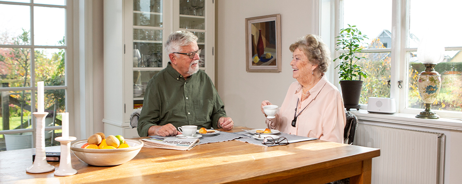 Senior couple having breakfast in kitchen with Doro Eliza smartcare hub on window sill