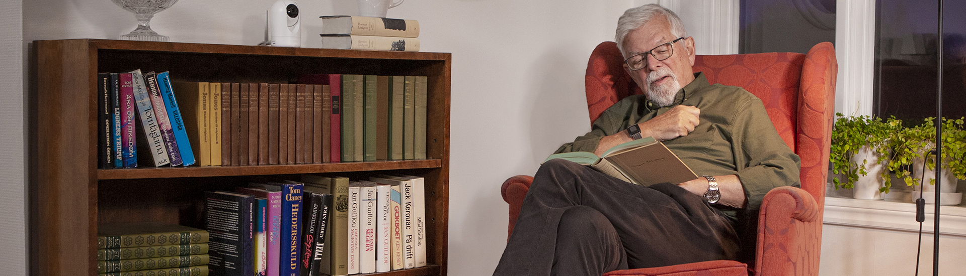 Senior man in armchair reading a book and Doro Visit camera on bookshelf