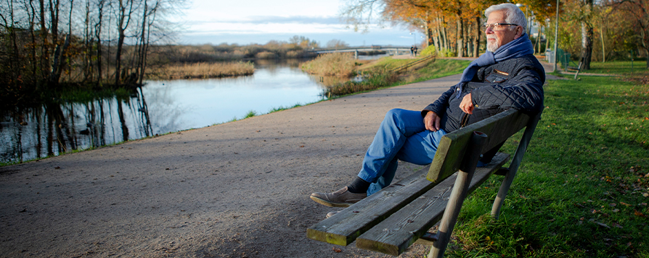 Senior man sitting on bench by a river