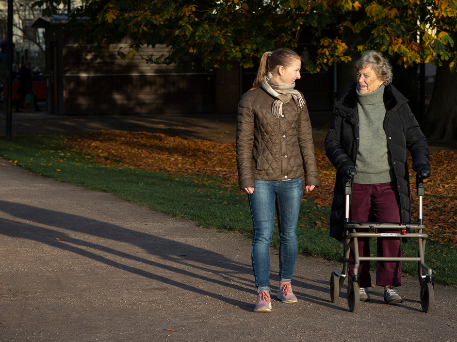 Senior woman and young woman walking and talking outdoors