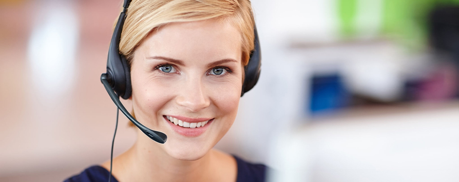 Young smiling woman in alarm reception with headset