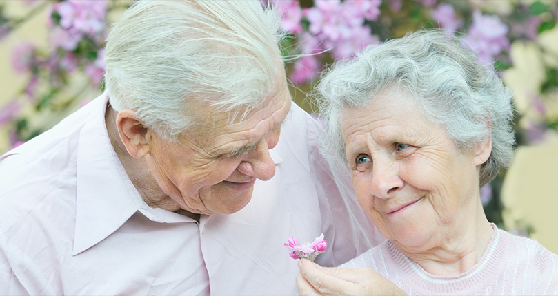 Senior couple smiling with flowers