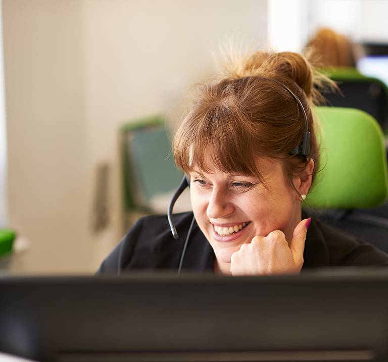 Young smiling woman with headset in alarm receiving centre