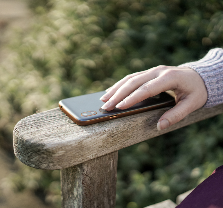 Hand touching a mobile phone laying on a wooden armchair rest