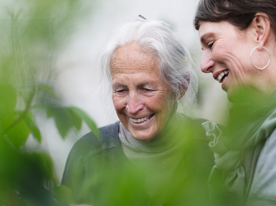 Senior and young woman laughing with plants in foreground