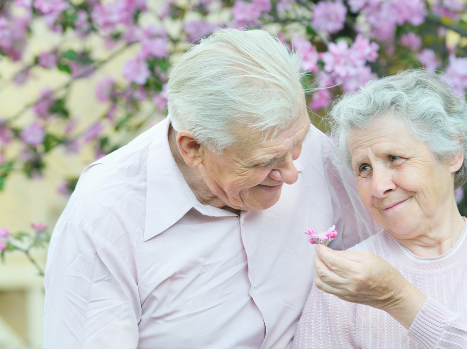 Senior couple smiling with flowers in background