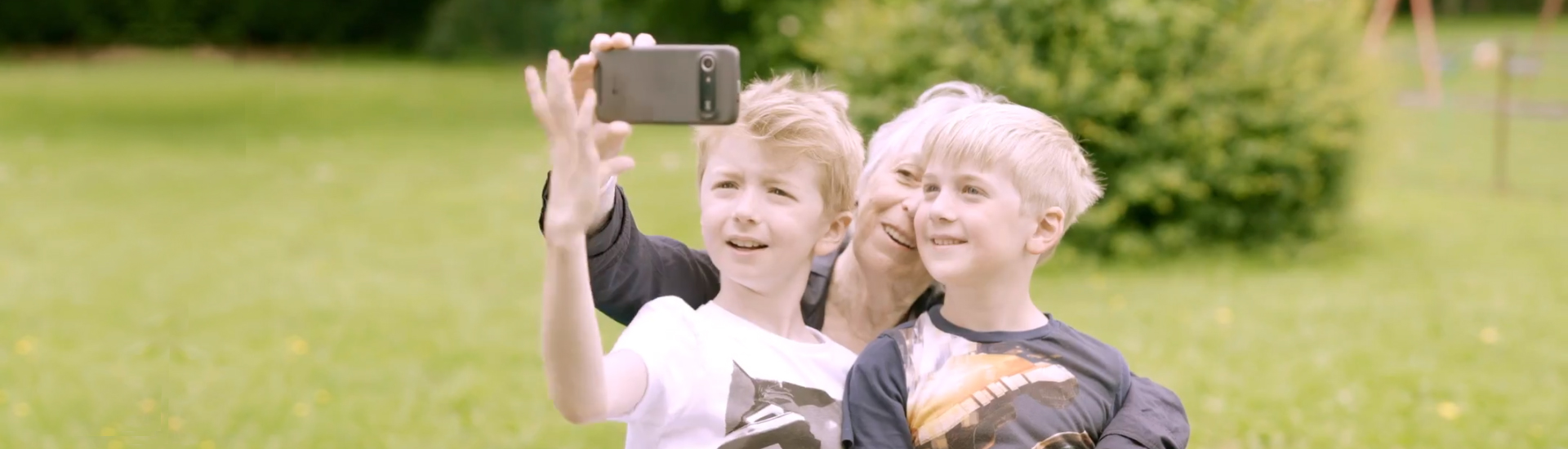 Woman snapping selfie with her grandchildren.