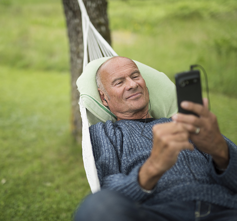 Lasse Holm in hammock using a Doro smartphone.
