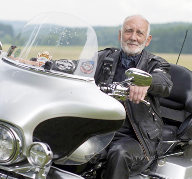 Man on a motorcycle with sidecar.