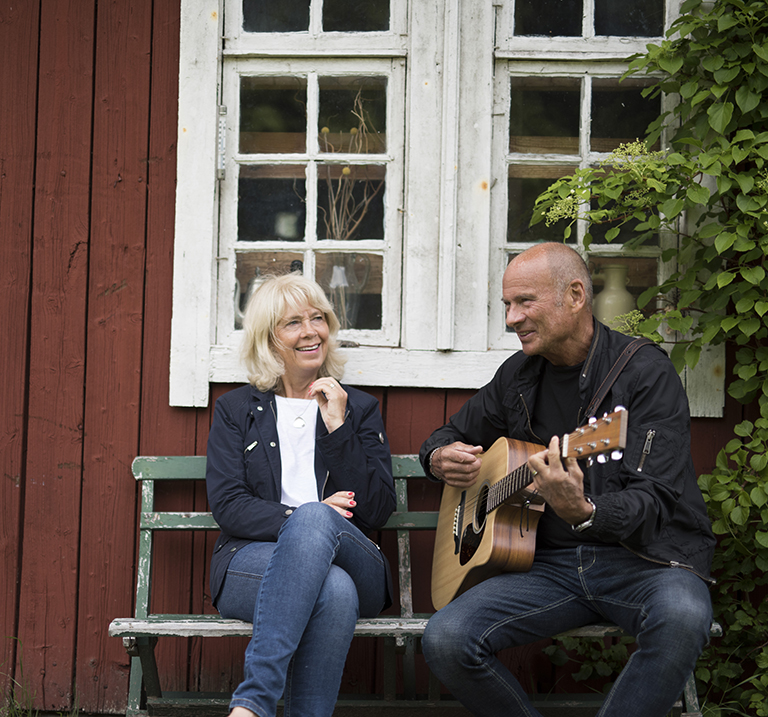 Lasse Holm playing guitar with woman outside a red cottage.