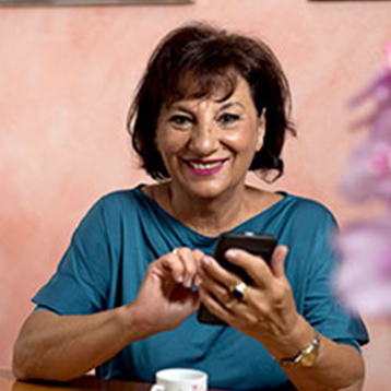Smiling woman using a Doro smartphone in a living room.