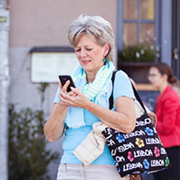 Woman using a Doro smartphone on city street.