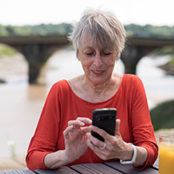 Woman using a Doro smartphone by a river.
