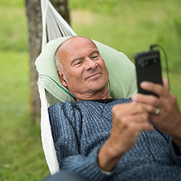 Lasse Holm in a hammock with a Doro smartphone.