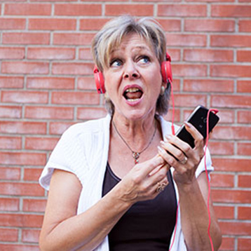 Woman listening to music with a Doro smartphone and headphones.