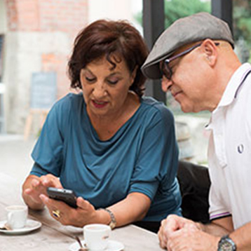 Three people at a table, looking at a Doro smartphone.