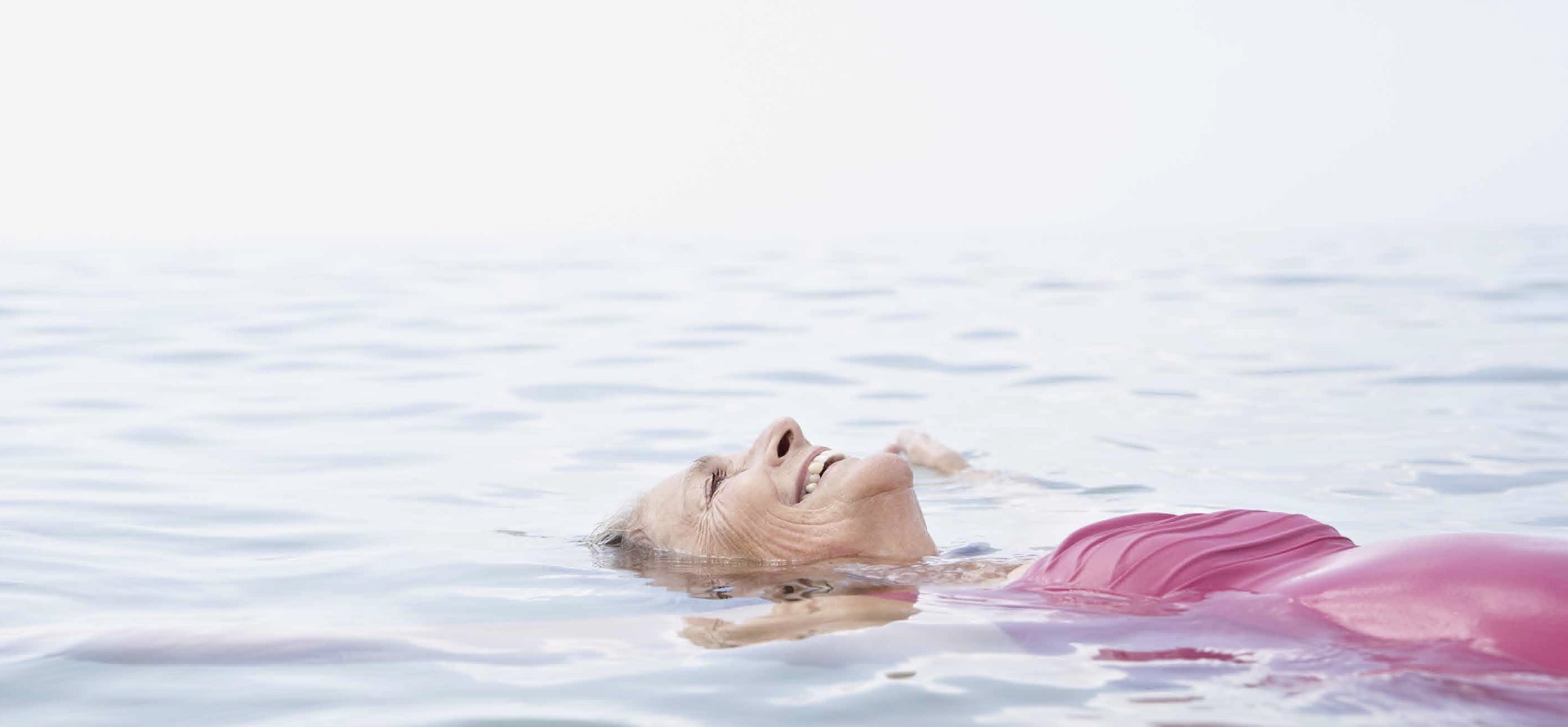 Happy woman floating on the surface of the sea.